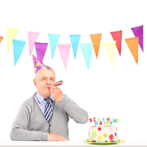Happy mature man with party hat blowing and a birthday cake